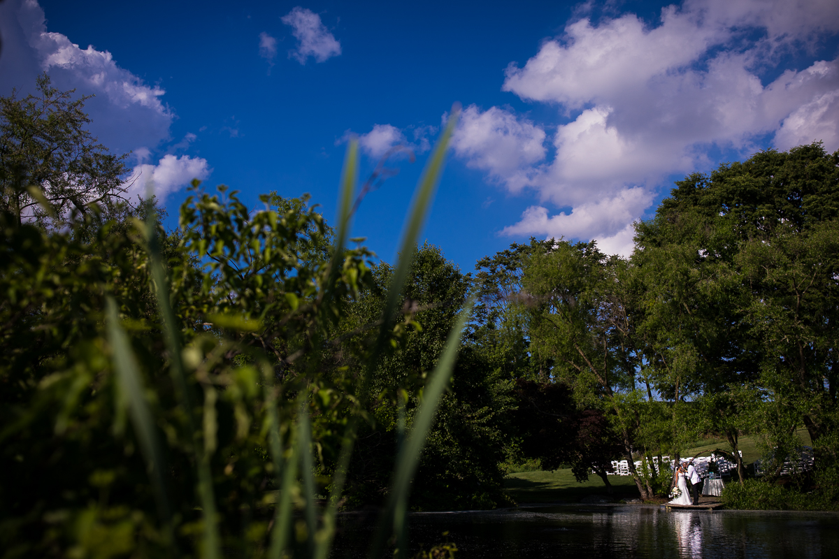 wide angle photo of bride and groom kissing after wedding ceremony while standing at edge of pond surrounded by trees and vibrant blue sky