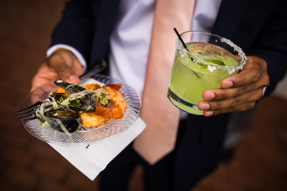 farm at eagles ridge wedding guest holds margarita and clams and shrimp on plate during cocktail hour