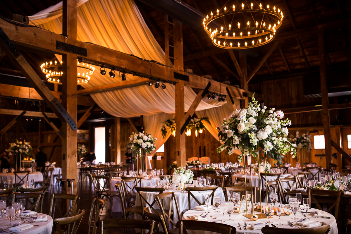 reception room at farm at eagles ridge with white linens and flowers and drapery throughout rustic chandeliers wood cross back chairs