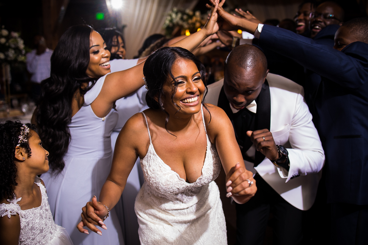 bride and groom walk under tunnel wedding party created with their hands everyone smiles