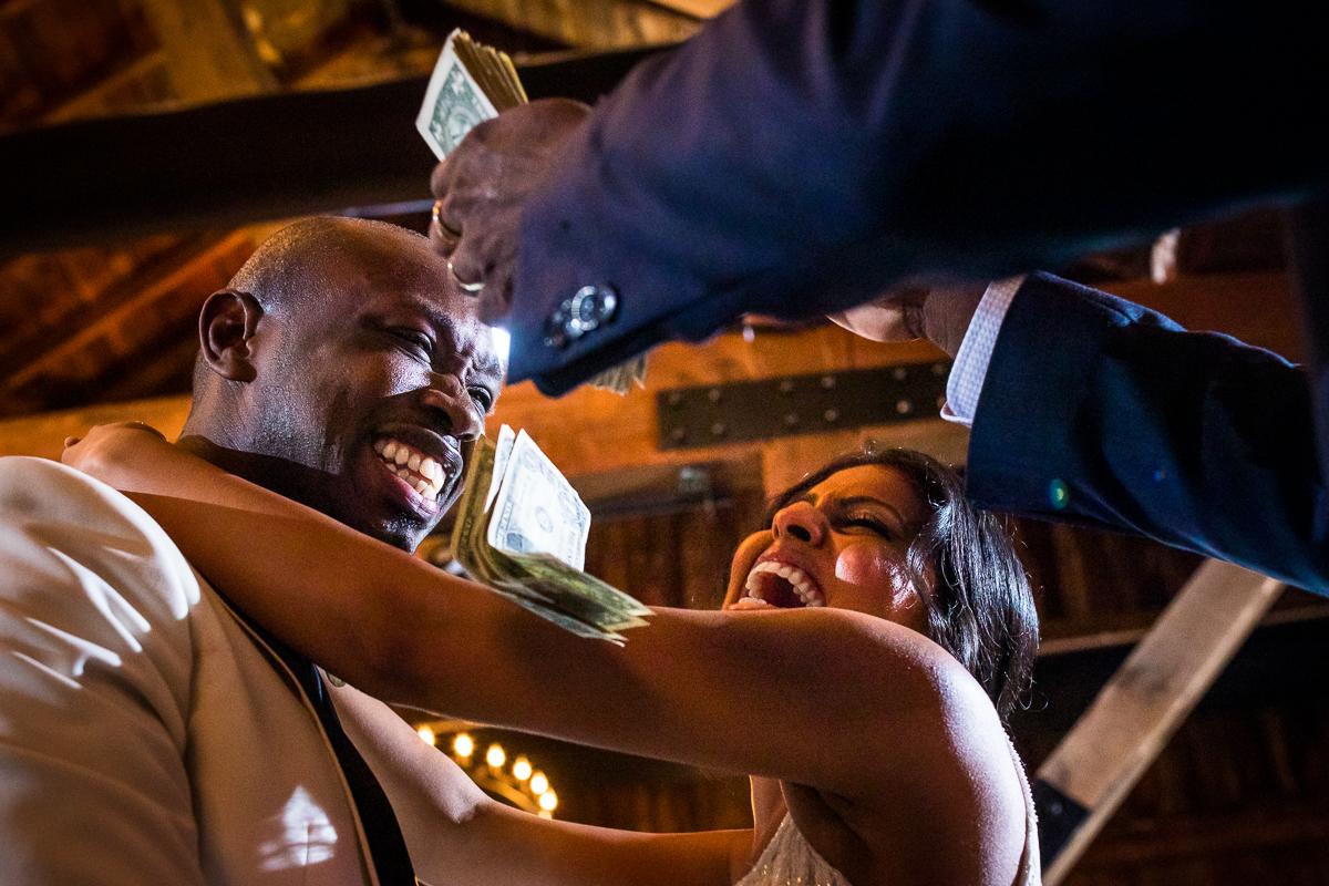 wedding guest throwing single dollar bills at wedding couple as they dance during wedding reception