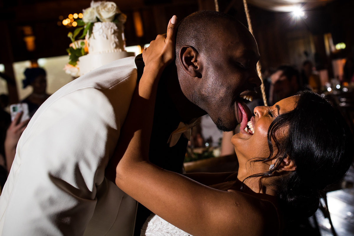 groom licking icing off bride's lips after sharing first taste of cake during wedding reception fun candid photographer