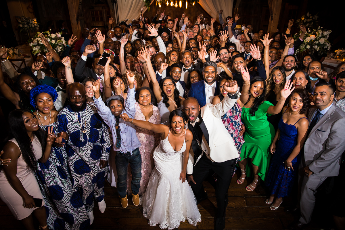 best Lancaster wedding photographer captures bride and groom with all wedding guests in huge group photo on dance floor during wedding reception farm at eagles ridge